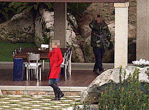 Una invitada pasea por la mansión de Berlusconi, acompañada de un guardaespaldas